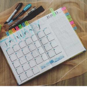 Un agenda est posé sur une table avec des stylos